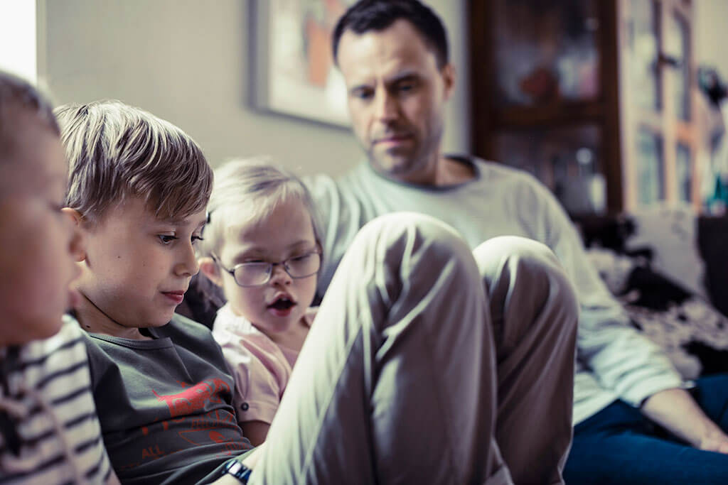 Father with children sitting on couch doing an activity